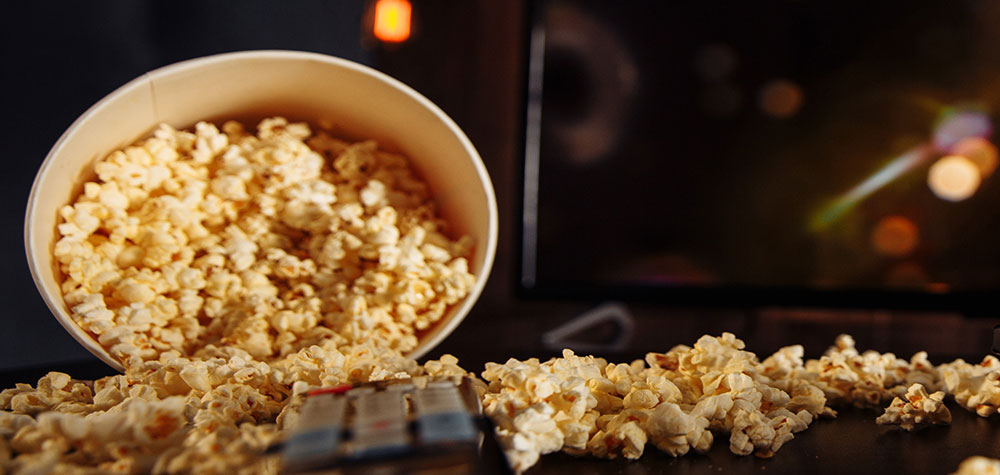 Popcorn scattered beside a remote